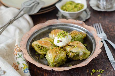 Turkish Dessert Baklava with cream on copper plate.
