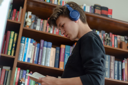 The teenage listens to music and reads book in front of library at home Stok Fotoğraf