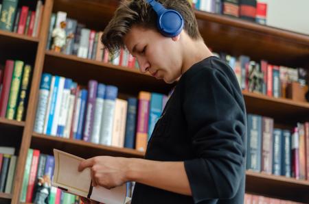 Nastolatek słucha muzyki i czyta książki przed biblioteką w domu