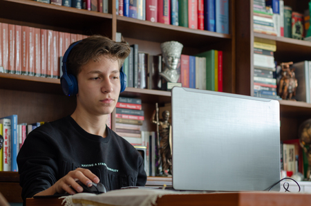 The teenage is  listening to music at home