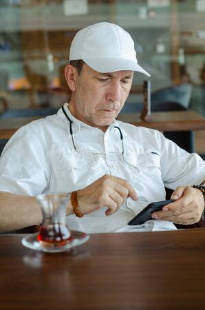 Portrait of serious man using smartphone at the cafe Stock Photo