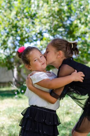 Twee schattige zussen knuffelen elkaar buitenshuis en oudere zus kust jongere zus.