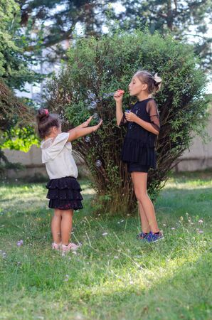 Two cute sisters are playing with soap bubbles in the garden Foto de archivo