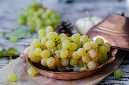 Bunch of white grapes in the copper bowl on wooden table. Foto de archivo - 133556701