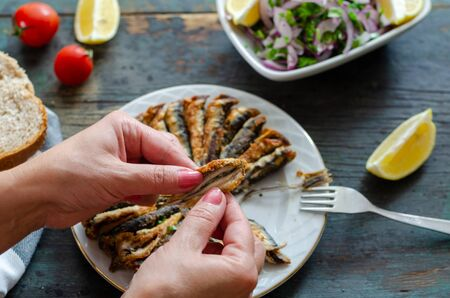 Fried anchovies fish and salad on wooden table.The woman is eating fish.