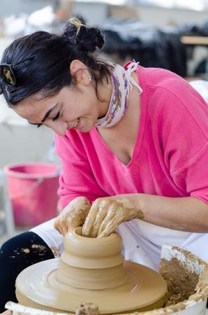 Eskisehir,TURKEY-September 10,2019: 13th.Eskisehir International Terra Cotta Symposium.The artist shows how to make bowl on potters wheel 新聞圖片