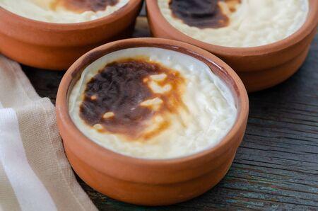 Turkish rice pudding sutlac, turkish dessert on wooden table.