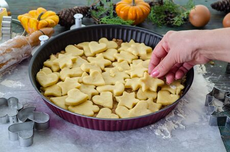 Apple pie ready to be baked in the oven, It  is covered with star and heart shaped cookies