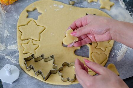 Woman is making Christmas gingerbread cookies in the kitchen.