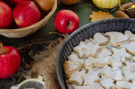 Fresh baked homemade apple pie on a wood table with cutter and apples.