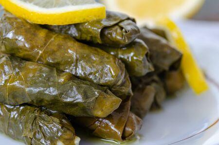 Traditional Turkish Dolma, Sarma or Dolmades,  Eating Traditional Mediterranean Dish Dolmadakia or Stuffed Grapes Leaves on Rustic Background