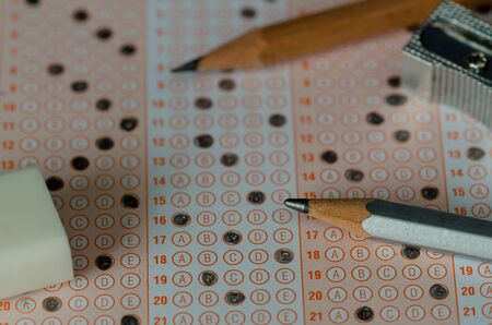 Pencils,, eraser and sharpener under standardized test form.selective focus and shallow depth of fieldEducation and exam concept Imagens