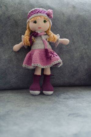 Knitted doll .It is handmade and on the sofa . Crochet stuffed doll.