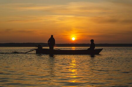 The fishermen and boat silhouette on the lake. Zdjęcie Seryjne