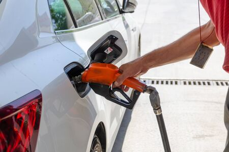 The worker filling up car fuel tank at gas station Stock Photo