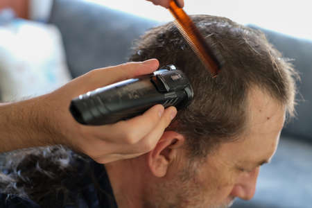 The young man is cutting father's hair with hair clipper during coronavirus quarantine isolation at home .Home haircut concept.