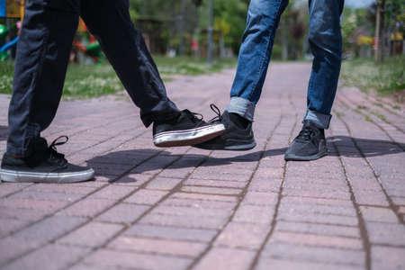 Foot shake style of greetings.Quarantine methods to control spread of coronavirus.Two friends bump feet outdoors.