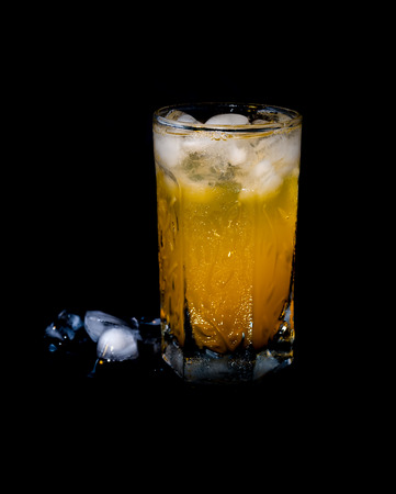 Full glass of orange juice with ice cubes over black background photo