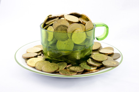 business supplies: Close up image of a transparent cup full of gold coins