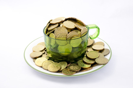 pecuniary: Close up image of a transparent cup full of gold coins