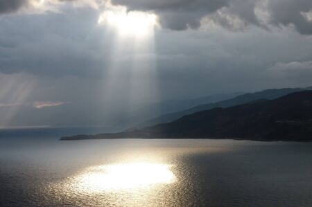 heavenly: Calm seascape with stormy sky where sun-rays get through the clouds.