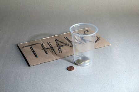 The plastic cup, coins and inscription Thanks photo