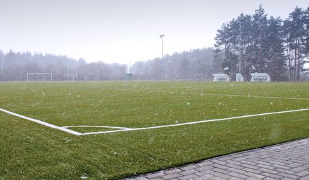 Football   soccer playground and snow showers in the spring photo