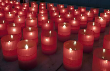 lighted candles in the red container in a church photo
