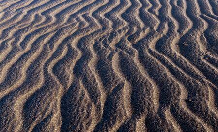 Close up view black beach sand background photo