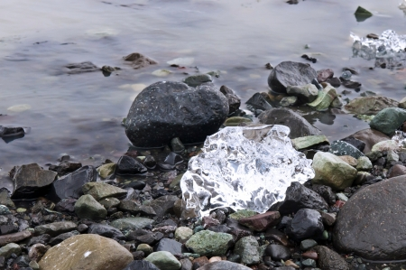 Black stone and white glacier ice on the shore of the lagoon Stock Photo - 14532393