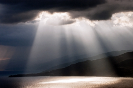 Sun shining through dark clouds on the sea