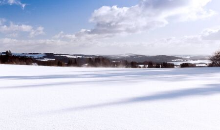 Winter landscape with white plain and mountains in the background photo