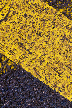 road surface: A closeup of a yellow line of road surface markings Stock Photo