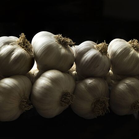 A string of garlic on the black background