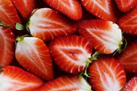 A closeup of fresh strawberries sliced into halves. Top view. Background Stock Photo