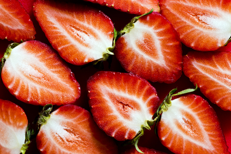 A closeup of fresh strawberries sliced into halves. Top view. Background Banque d'images