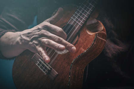 Hands of a man playing the ukulele. Folk music performer on ukulele. Photo with toning and shallow depth of field. Selective focus.