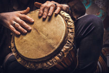 A man playing an ethnic percussion musical instrument jembe