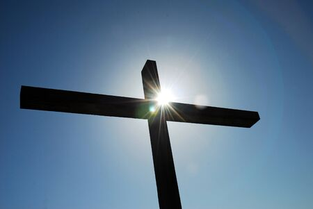 easter triduum: Cross against blue sky with bright sunburst at crossing of beams