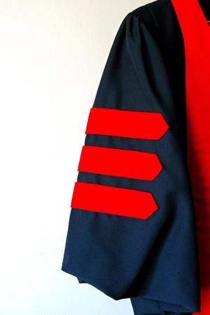 regalia: Sleeve of black graduation robe with three red doctoral stripes Stock Photo