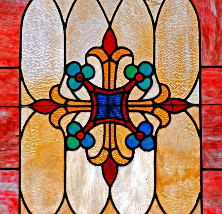 Stained glass window depicting cross with flowers