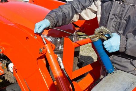 greasing: Arduo trabajo el mantenimiento de la pistola de engrase del pist�n con Foto de archivo