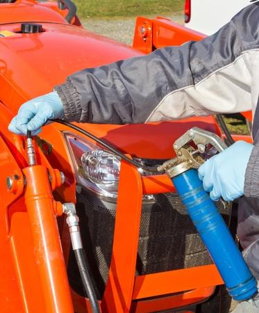Hard at work maintaining piston with greasing gun