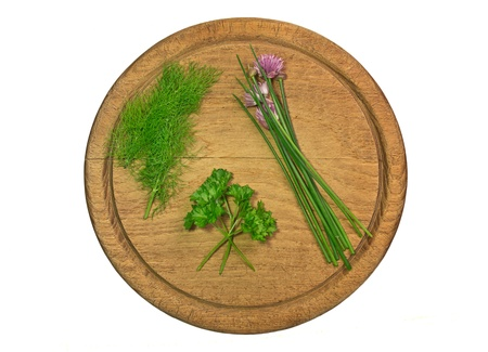 Assortment of herbs and spices on natural wood cutting board photo
