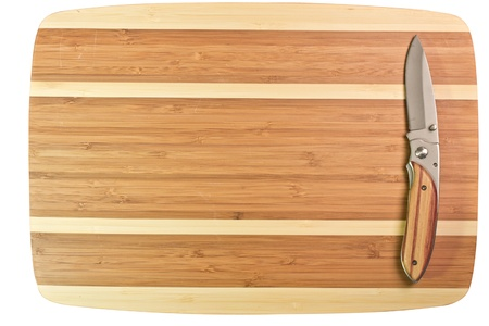 wood cutter: Natural bamboo surface with sharp steel knife on top Stock Photo