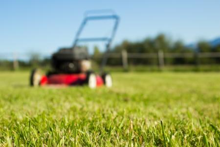 フォア グラウンドで新鮮なカット草で焦点が合っていない赤の芝刈機 写真素材
