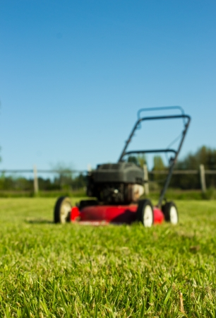 cut grass: Red Lawn mower out of focus with freshly cut grass in foreground