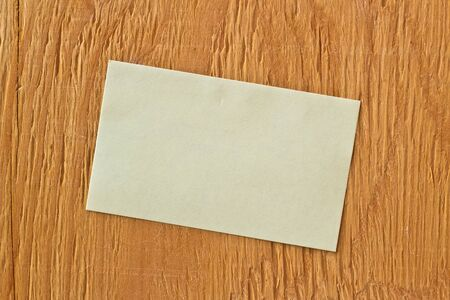 posted: Yellow sticky note posted on ply wood background