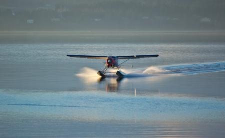 plane landing: Seaplane landing in water with sunset to the left