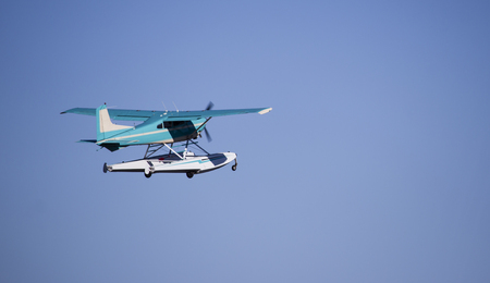Turquoise sea plane taking off against blue sky photo